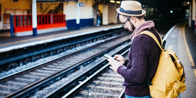 Man standing on station platform, browsing the web on his mobile phone